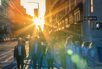 Fotomurales - Colorful sunlight shines on crowds of people in motion through a busy intersection in New York City