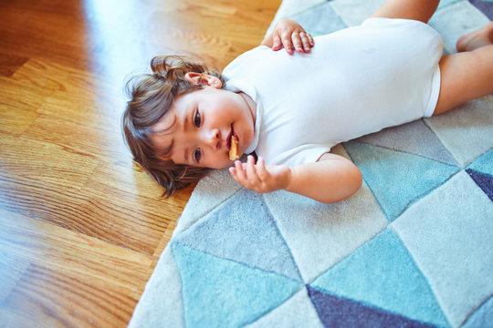 Beautiful toddler child girl wearing white bodysuit lying down on the carpet