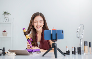 Portrait young asian woman review giveaway gift product to fan following channel, record video make up cosmetic at home. Online influencer girl social media marketing live steaming smartphone concept