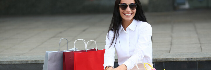 Portrait of cheerful female in stylish sunglasses looking at camera with happiness. Smiling woman sitting on stairs and putting hands on knees. Fashion and shopping concept. Blurred background Fotobehang