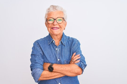 Senior grey-haired woman wearing denim shirt and glasses over isolated white background happy face smiling with crossed arms looking at the camera. Positive person.