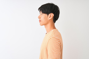 Young chinese man wearing casual striped t-shirt standing over isolated white background looking to side, relax profile pose with natural face with confident smile. Fototapete