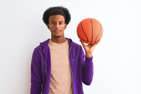 Young african american sportsman holding basketball ball over isolated white background with a confident expression on smart face thinking serious