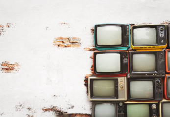 Retro televisions pile on floor in old room with white wall. Antique and vintage home decoration style.