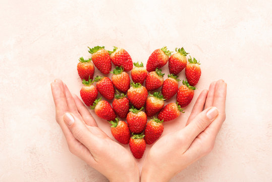 Strawberries, heart and woman's hands. Valentine's day concept