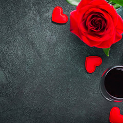 Valentines day or romantic meeting concept. Red rose and red wine on gray background