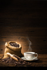 Poster Café en grains Cup of coffee with smoke and coffee beans on old wooden background