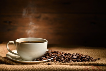 Keuken foto achterwand Cafe Cup of coffee with smoke and coffee beans on burlap sack on old wooden background