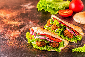 Falafel and fresh vegetables in pita bread.