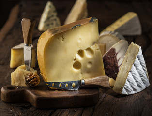 Wall Mural - Piece of cow's milk Maasdam cheese on wooden board. Range of cheeses at the background.