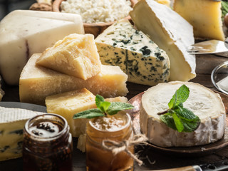 Wall Mural - Cheese platter with organic cheeses, fruits, olives and jam on wooden background. Tasty cheese starter.