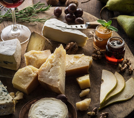 Wall Mural - Cheese platter with organic cheeses, fruits, nuts and wine on wooden background. Top view. Tasty cheese starter.