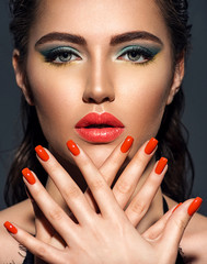 Beautiful woman with bright red lipstick and  nails. Gorgeous girl with blue eye makeup.
