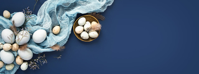 Easter banner with painted eggs and napkin on dark blue backround. Top view, flat lay with copy space. Fotomurales