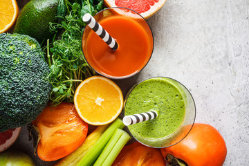 Green and orange detox smoothie in glass. Ingredients for detox smoothie background, copy space. Healthy food concept.