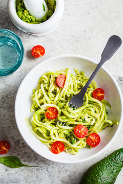 Zucchini pasta with pesto, avocado and tomatoes in white plate, top view. Raw vegan food concept.