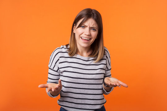 What do you want? Portrait of confused annoyed woman with brown hair in long sleeve shirt raising arms, asking and having no idea what happening. indoor studio shot isolated on orange background