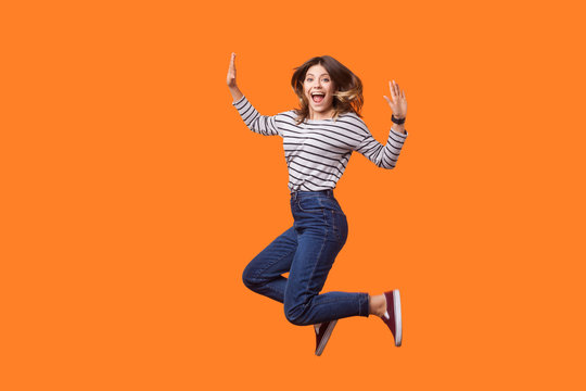 Full length portrait of extremely happy pretty woman with brown hair in long sleeve shirt and denim jumping for joy or flying, celebrating success. indoor studio shot isolated on orange background