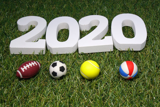 White Wooden 2020 with Football Tennis ball Volleyball Rugby on green grass background
