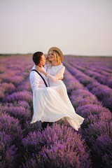Papiers peints Lavande Happy groom holding his bride in his arms in blooming lavender field at sunset