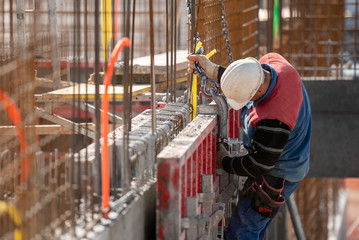 Fototapeta Male construction worker installing concrete retaining wall rebar on construction site obraz