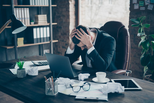 Photo of helpless business guy crumple papers holding head hands need rest work day night workaholic tired powerless wear black blazer shirt suit sitting chair office indoors