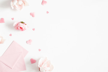 Valentine's Day background. Pink flowers, envelope, hearts on white background. Valentines day concept. Flat lay, top view, copy space