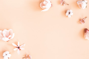 Flowers composition. Frame made of pink flowers on pastel beige background. Flat lay, top view,...