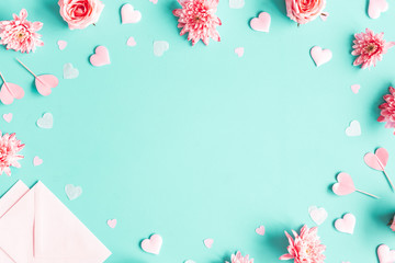 Valentine's Day background. Pink flowers, envelope, hearts on pastel blue background. Valentines day concept. Flat lay, top view, copy space