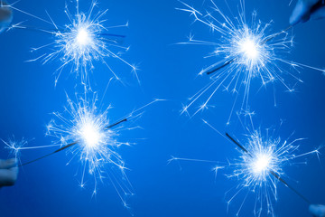 Close up of Bright burning four sparklers in hands on a blue background.