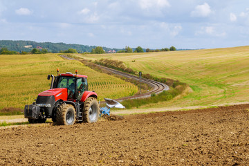 Farmer in red tractor preparing land with plow for sowing Fotomurales