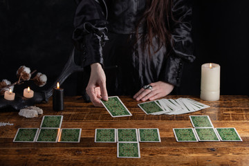 Female tells the future with playing cards. Tarot card concept on the table. Prediction of the future. Fortuneteller hands in black vestments.Psychic.