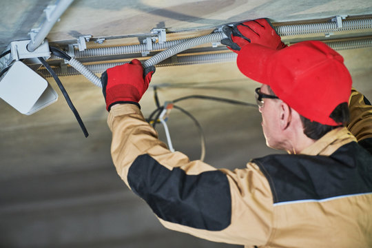 electrician service. Installer works with cable on ceiling