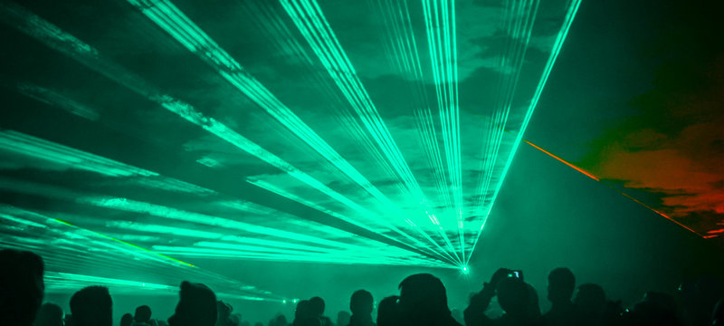 colorful outdoor laser show with silhouette of people