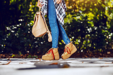 Cropped picture of girl in jeans walking in park at autumn.