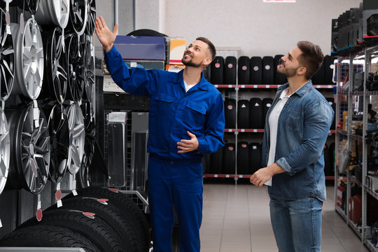 Male mechanic helping client to choose alloy wheel in auto store