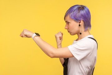 Side view of determined young hipster woman with violet dyed short hair in denim overalls punching with fist, showing boxing gesture, looking confident purposeful. yellow background, studio shot