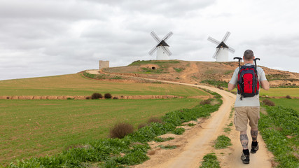 A hiker with a backpack and walking sticks reaches two beautiful old white windmills in the rural area of La Mancha in central Spain. It's cloudy.