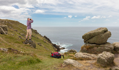 A hiker with binoculars looks out to sea at the Lands End lighthouse in south-west England. The man is standing on a rock on the high cliffs.