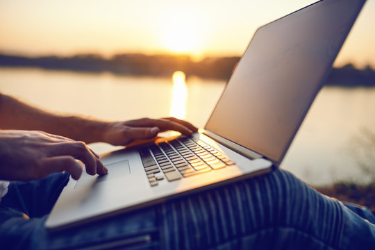 Close up of Caucasian man sitting in nature and using laptop. In background is river and sunset. Selective focus on hands.