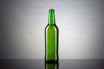 Cold unopened bottle of beer with cap on white background. Glass of refrigerated wheat or lager beer on bright background