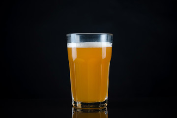 Fresh and cold glass craft beer with white foam on top on black background with space for text. Foamy wheat or lager beer on dark background