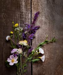 Wild flowers on old grunge wooden background ( lupine dandelions thyme mint bells rape).