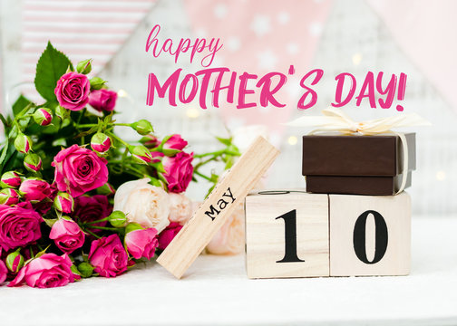 May 10 date on a wooden calendar, roses, holiday flags and a garland on a white background. Mother's day concept
