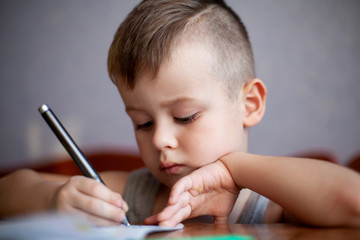 Closeup portrait of cute little boy drawing picture. The beautiful, emotional face of a child of four years.