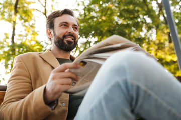 Image of handsome adult man reading newspaper on bench in park