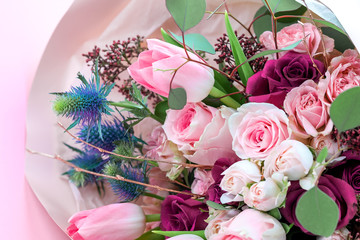 A closeup bouquet of roses and tulips decorated with leaves and twigs of other beautiful plants. Holiday concept. Flowers for Mother's Day. Copy space. Fotobehang