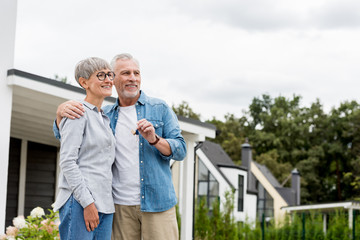 Spoed Foto op Canvas Hoogte schaal mature man holding keys of new house and hugging smiling woman