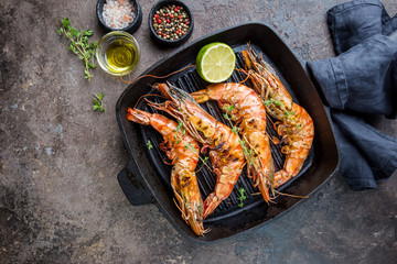 Grilled giant tiger prawns in frying pan with lemon and spices on vintage dark background, top view, copy space. Seafood dinner.