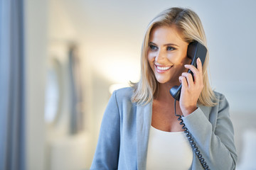 Businesswoman talking on the phone in hotel room
